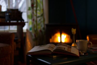 Open book in front of a fireplace.
